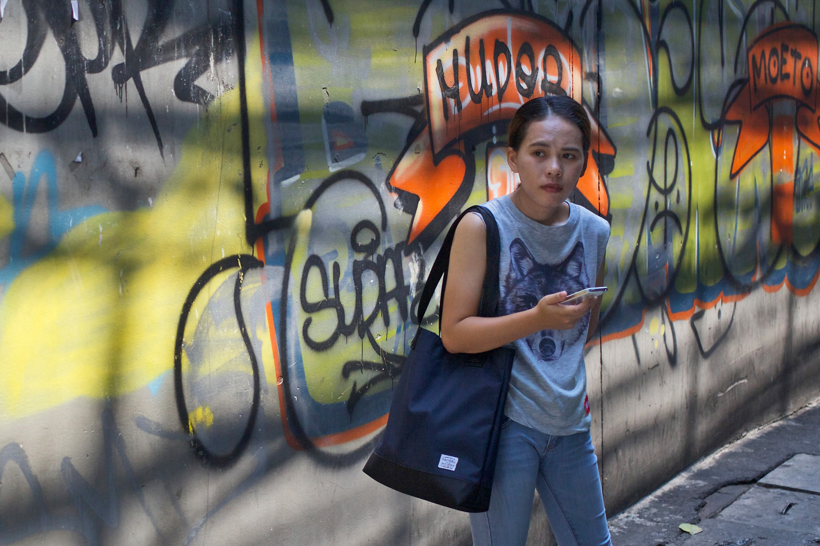Woman looking anxious in front of graffiti scrawls