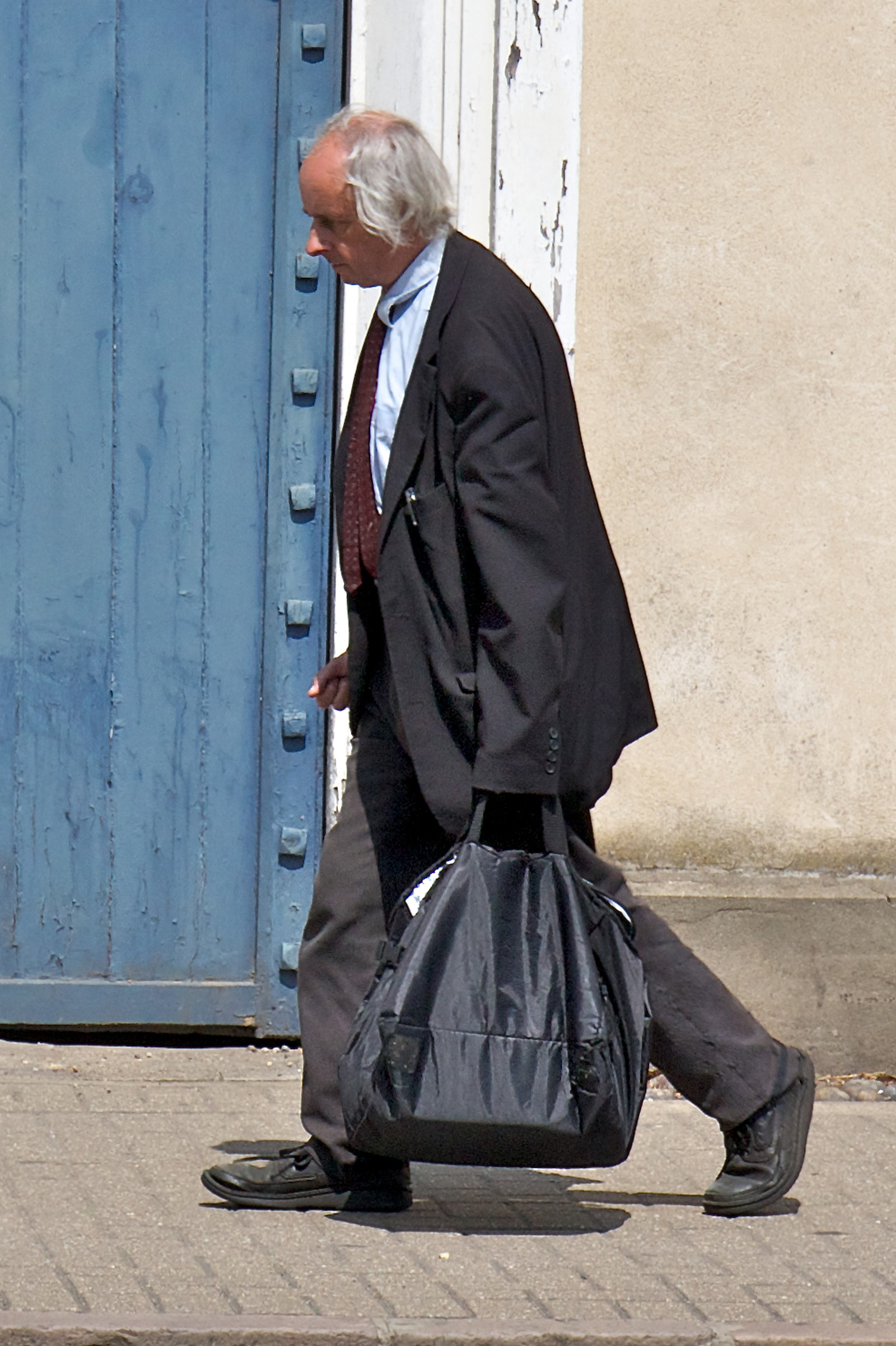 Man carrying a lot of books in a black bag