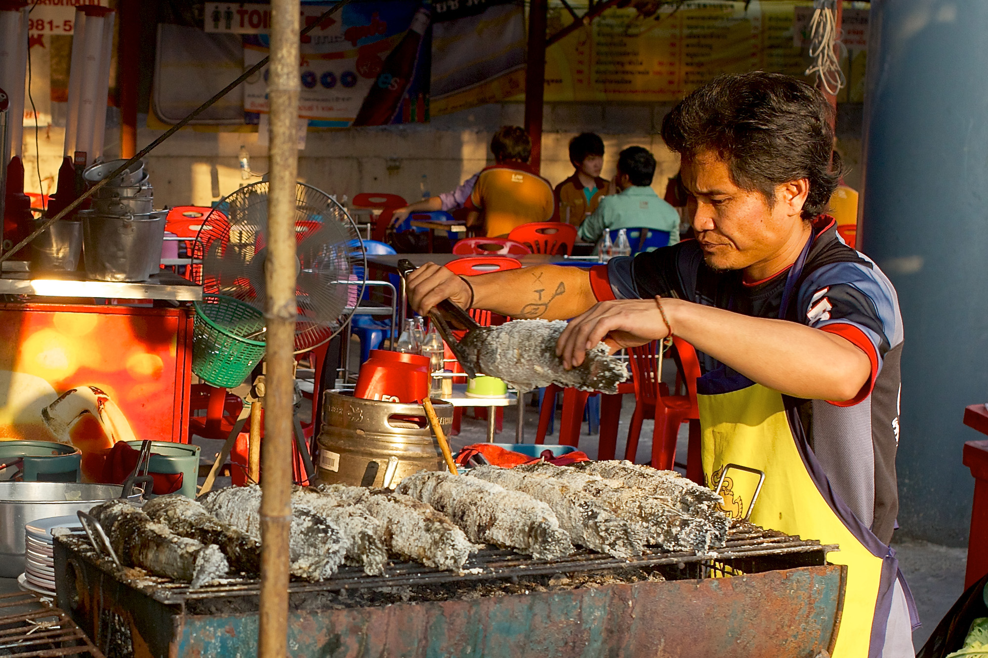 Man cooking fish in golden sunlight