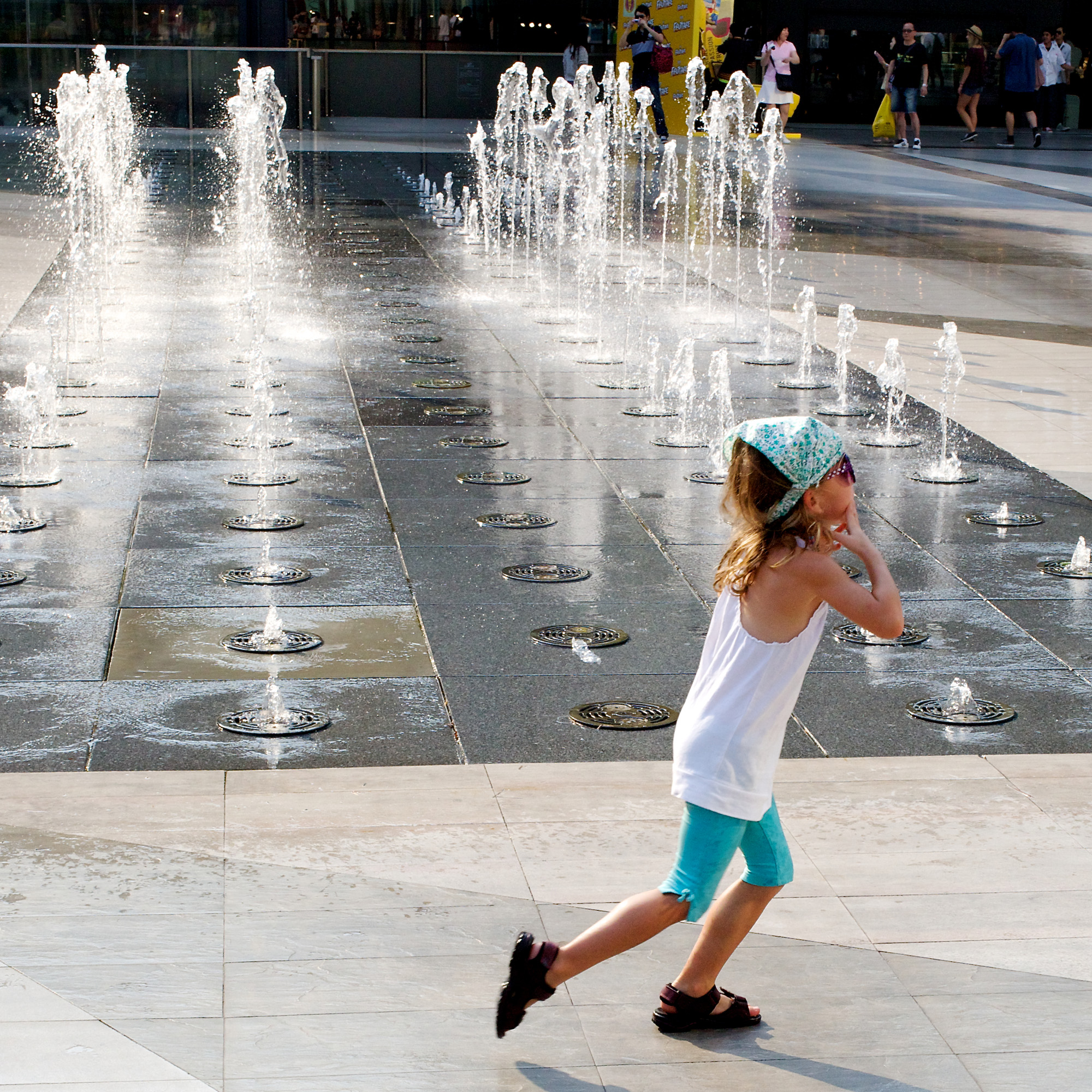 small girl playing in fountain
