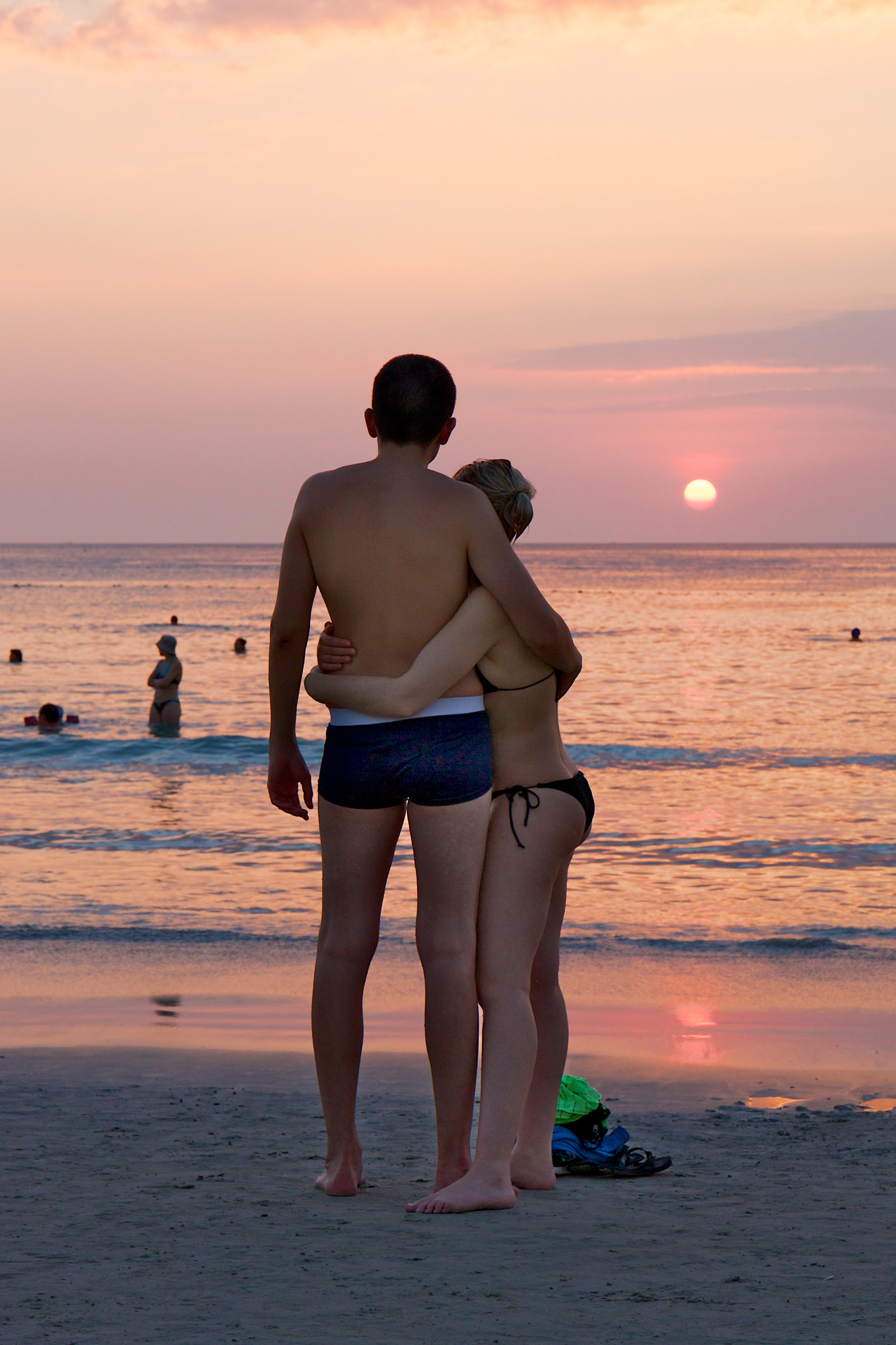 Couple on the beach, watching sunset