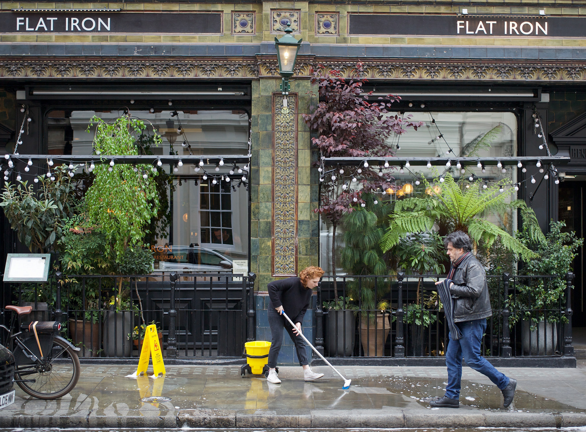 cleaning pavement outside restaurant