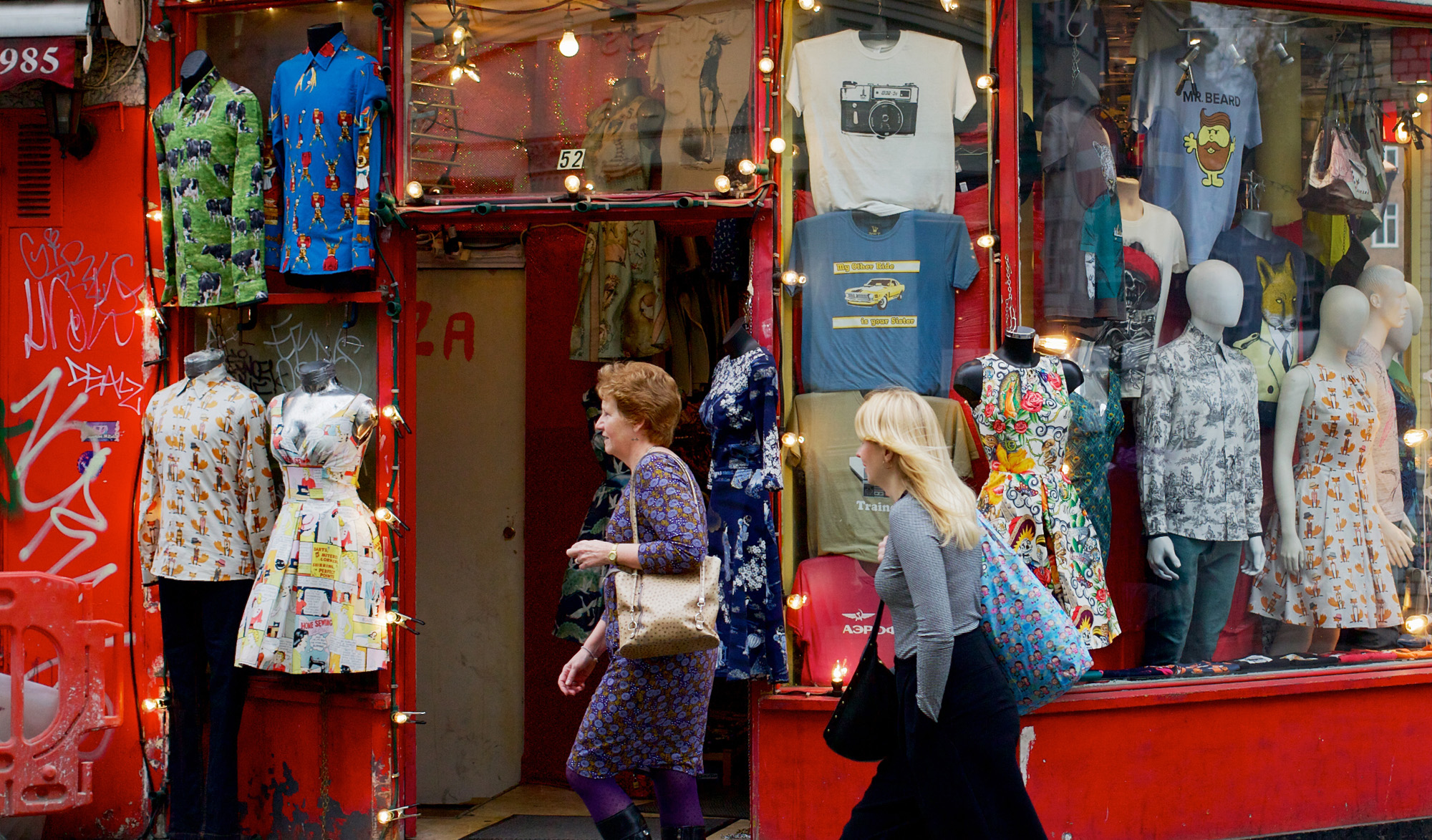 women walking past vintage clothes store