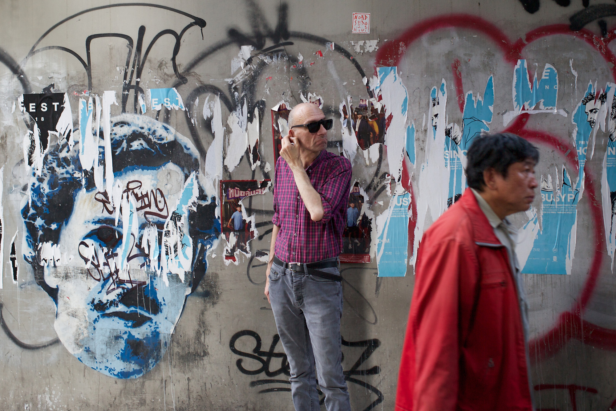 man in front of graffiti wall, looking anxious