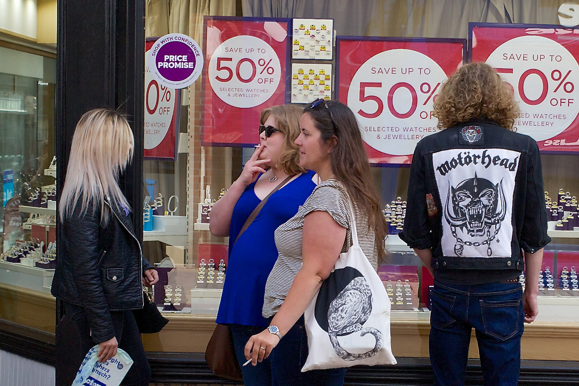 Jeweller's shop window being browsed by heavy metal fan, while three women walk past