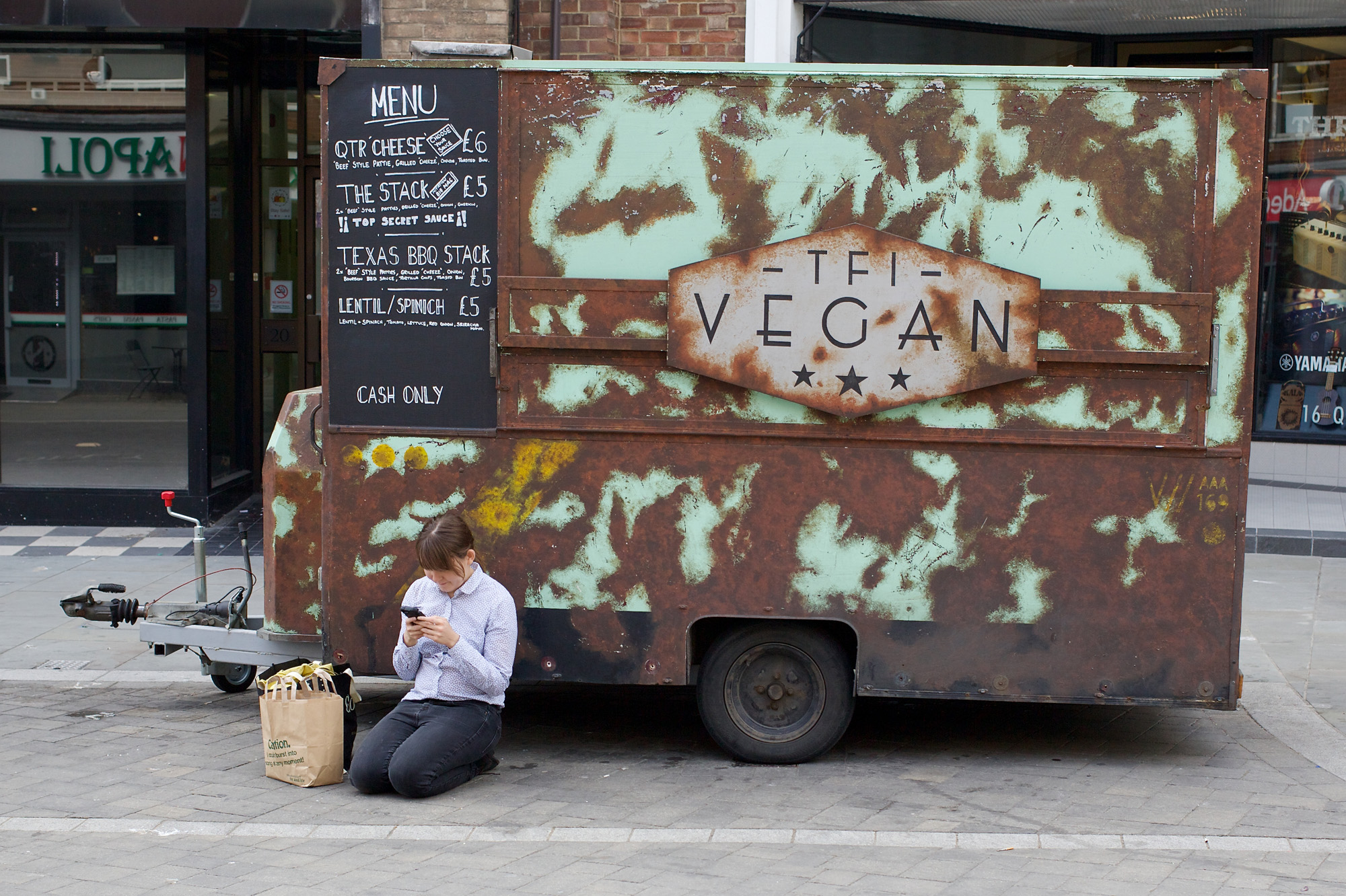 girl crouched beside rusty food van