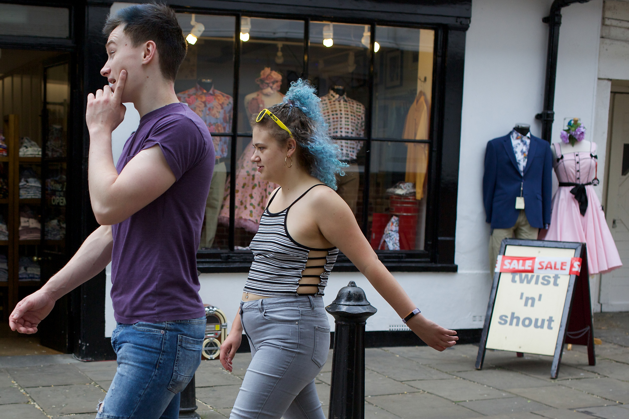 couple walking past vintage store