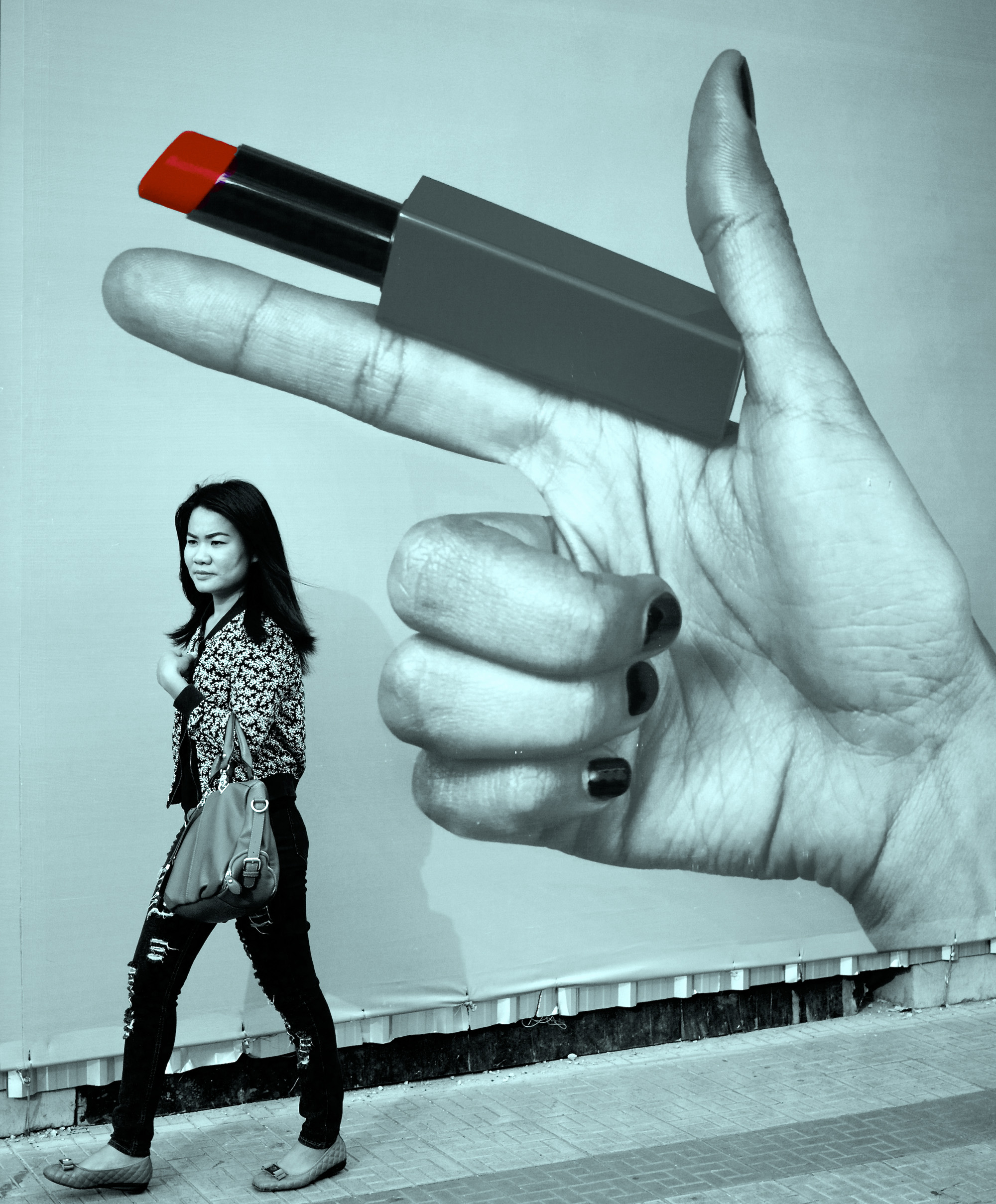 woman walks past a poster featuring a gigantic hand holding a lipstick as if it were a gun