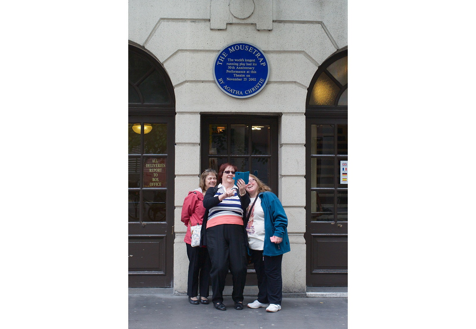 three women, outside theatre with The Mousetrap plaque