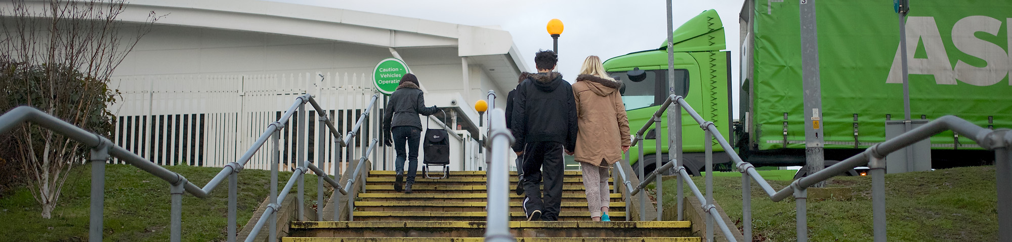 Ultra-wide screen image of people walking up steps