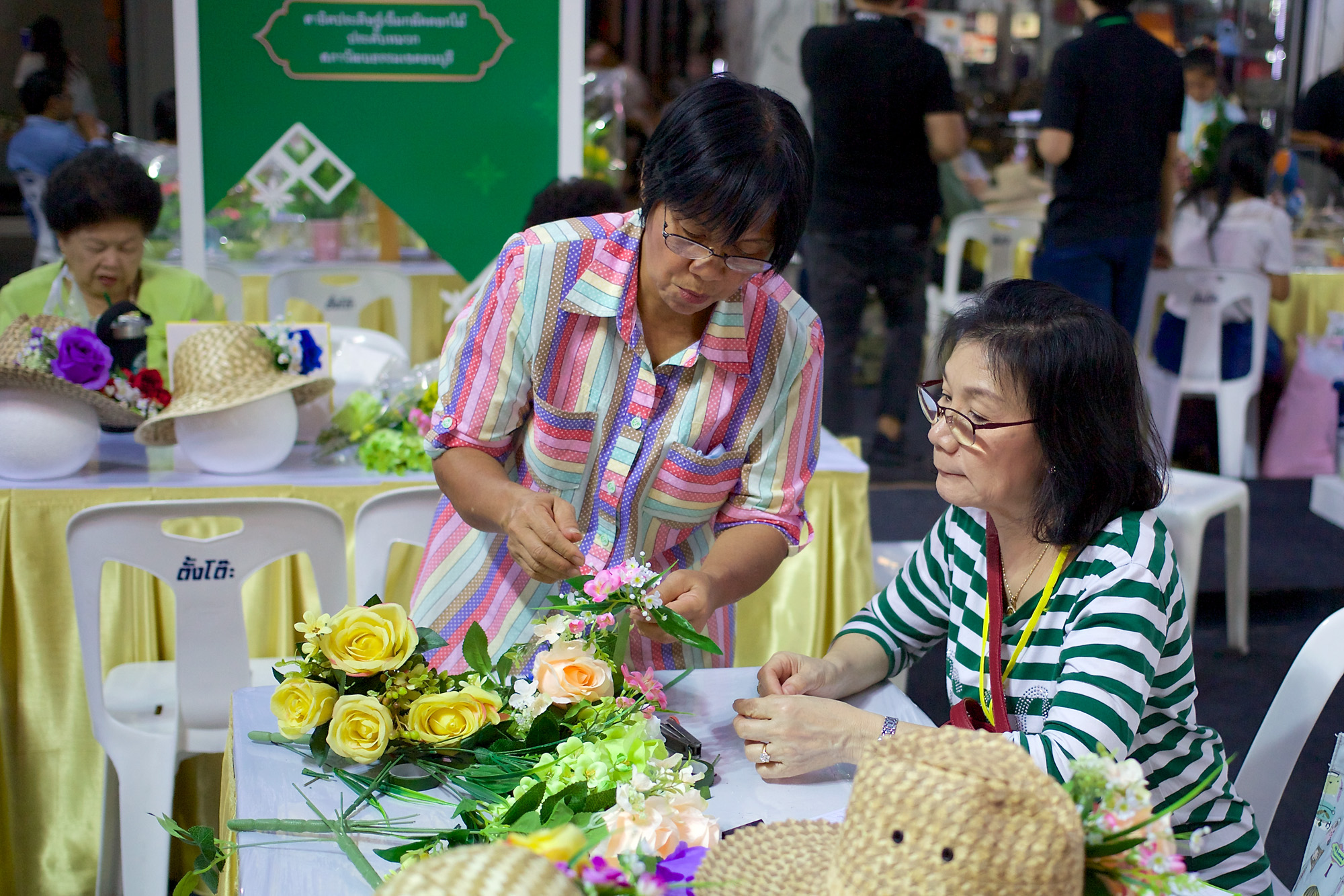 Two women arranging flowers with great concentration.