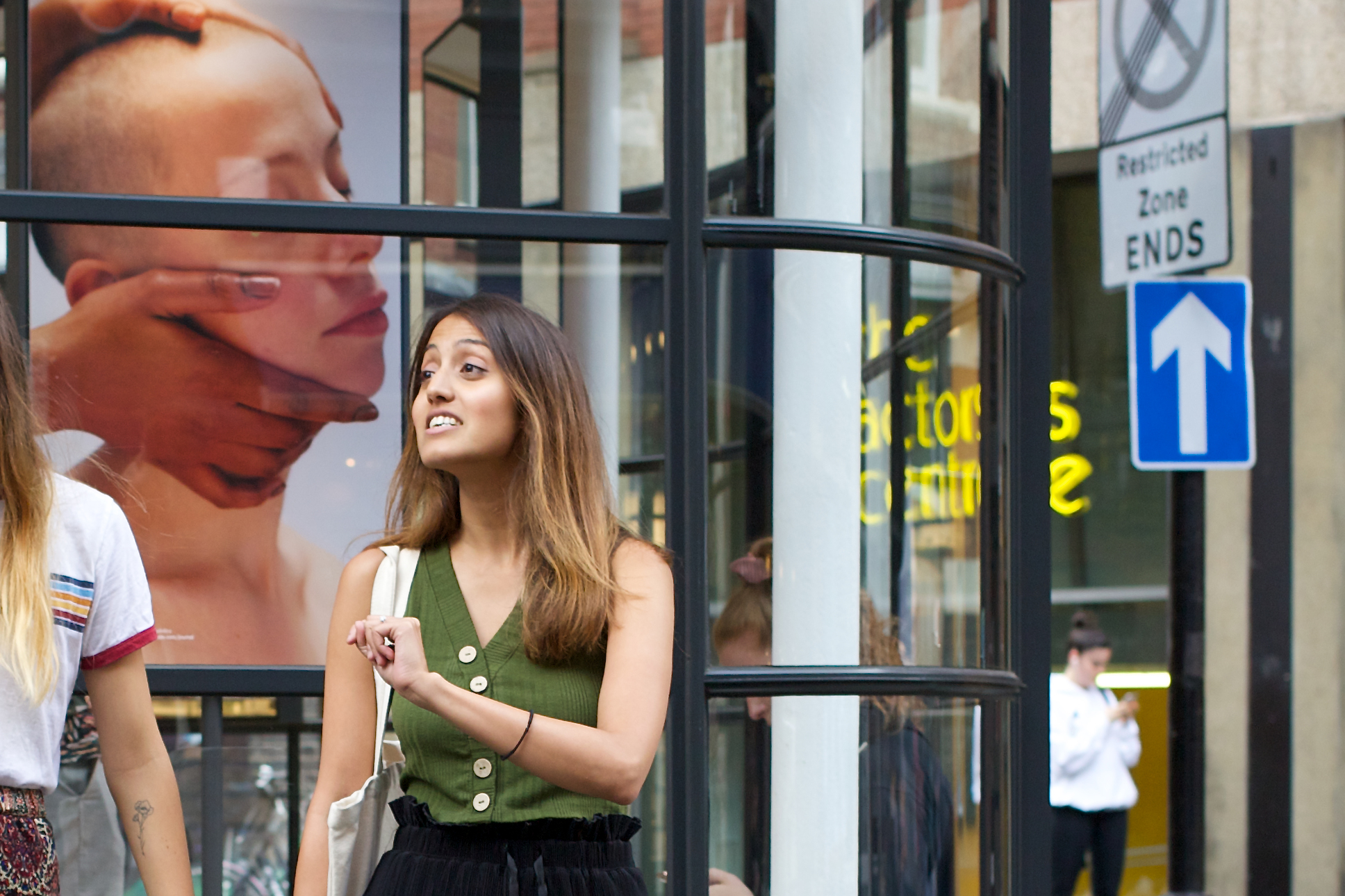 Woman in animated conversation. In a window behind her is a poster of person with shaven head being massaged by strong hands