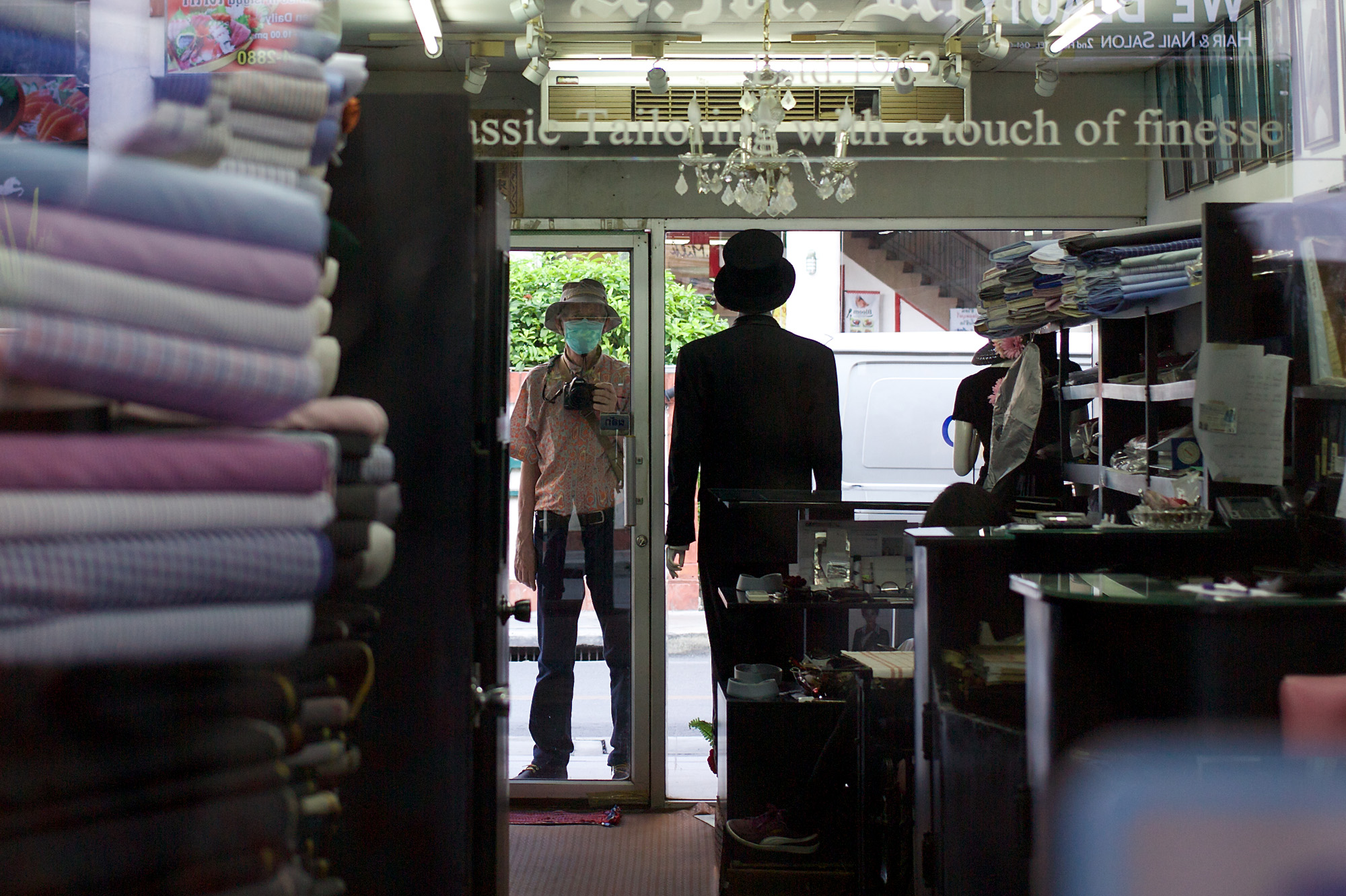 the photographer, looking into a tailor's shop, reflected in a mirror