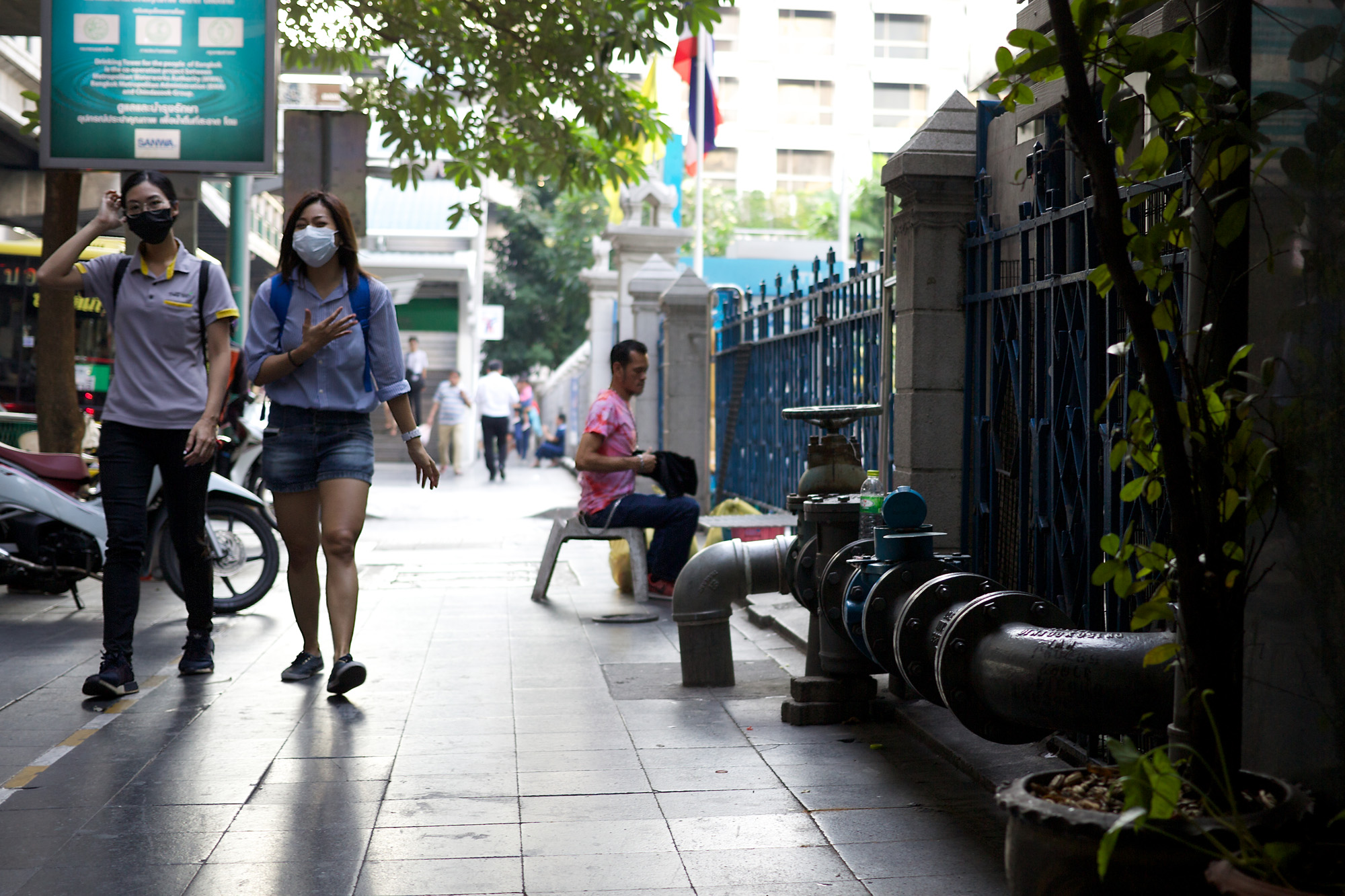 two health workers in masks, walking past a massive fire hydrant