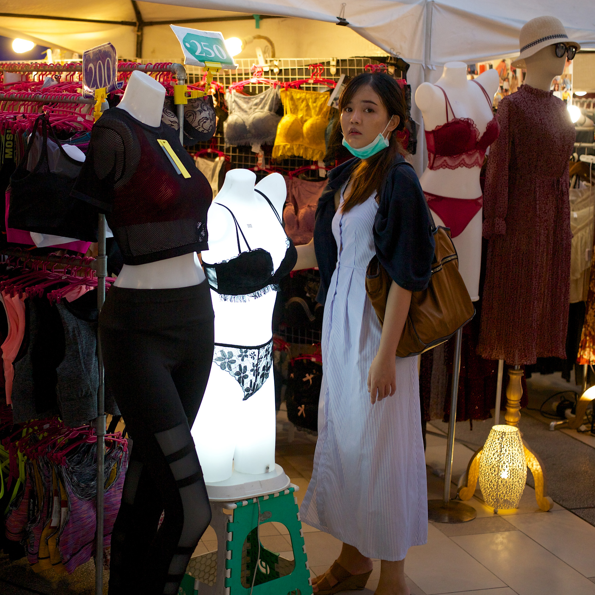 young woman with mask under chin, standing in front of an illuminated underwear mannequin