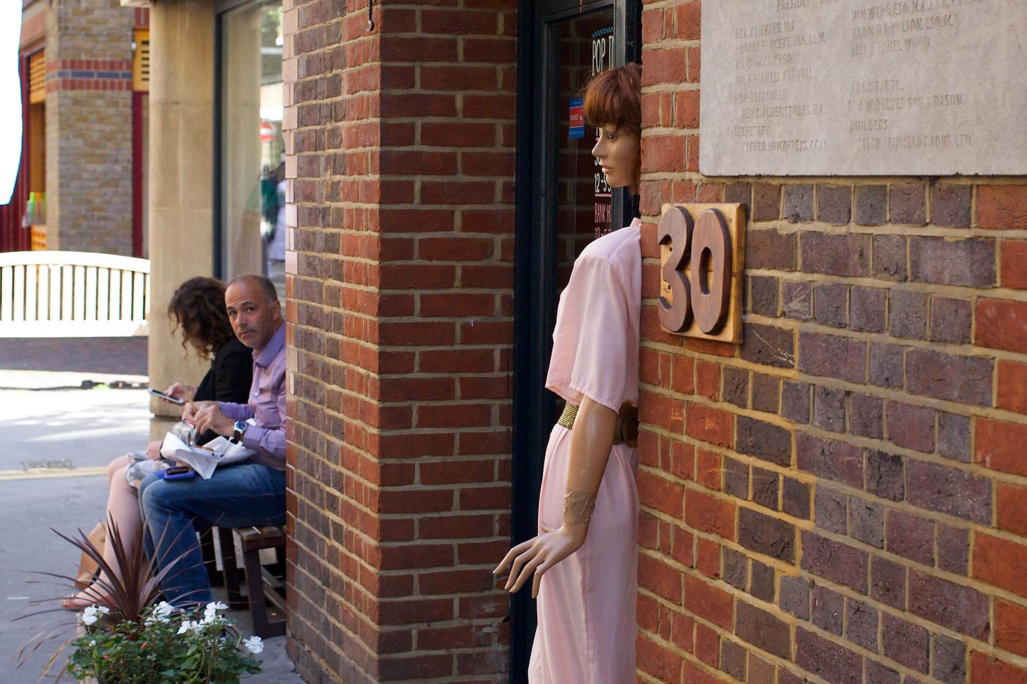 mannequin peeps out of shop door